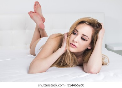 Sexy girl in white corset and panties underwear lying on the bed, emotive expression