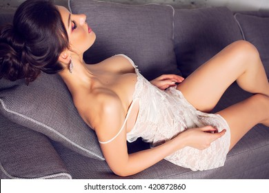 Sexy girl in a white peignoir. Elegant woman in a white transparent chemise. Brunette with huge breasts. Model with silicone tits. Luxurious body