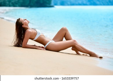 Sexy girl in white swimsuit laying on the sand at tropical beach in Thailand