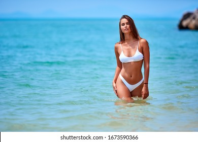 Sexy girl in white swimsuit walking at the tropical water in Thailand
