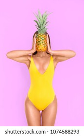 Sexy girl in a yellow bathing suit with a pineapple on a pink background