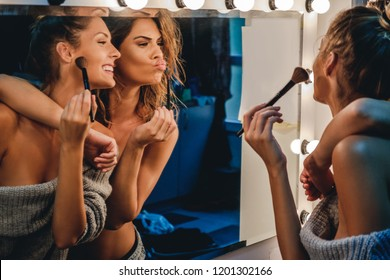 Sexy girls are hugging and having fun in front of vanity mirror