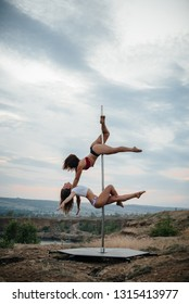 Sexy girls perform amazing numbers on the pylon during sunset. Sport.