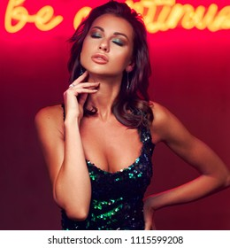 Sexy glamor woman in green sequins evening dress in night club or bar against red wall with neon letters. Fashion style portrait