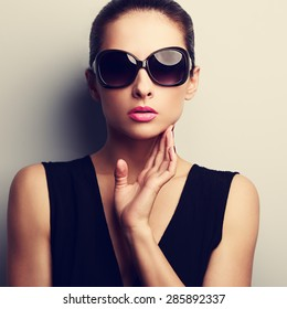 Sexy glamour female model in trendy sun glasses with hand at face. Closeup vintage portrait