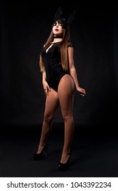 Sexy glamour girl in bodysuit, female wearing lingerie and shoes on black background with makeup and mask