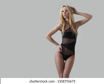 Sexy glamour model in black swimsuit on a white background