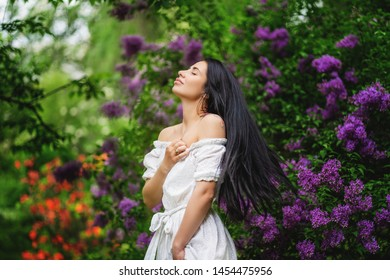 Sexy Glamour Summer Beautiful Woman with Healthy and Beauty Dark Hair with violet spring flowers over nature background. Fairy
