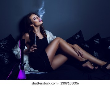 Sexy glamour woman in club dress with long legs smoking hookah. Enjoing of smoking, relax