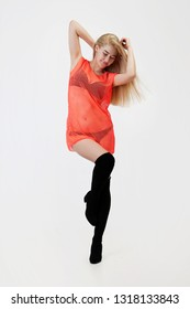 Sexy go-go dancer in orange mesh cape and black suede high boots. In a studio, on a white background. Without looking camera.