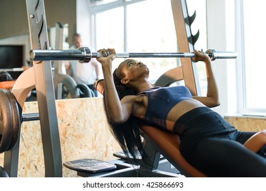 Sexy gorgeous african american woman training with barbell at the gym