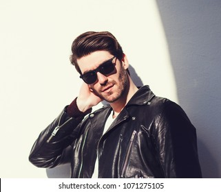 Sexy gorgeous stylish man in leather jacket. City style. Charming man with sunglasses outdoors.