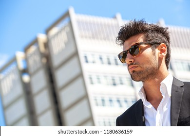 Sexy gorgeous stylish man. Sunglasses. City style. A beautiful and charming man with sunglasses outdoors. Stubble and blacks hair. Intense light. White shirt and stylish jacket.