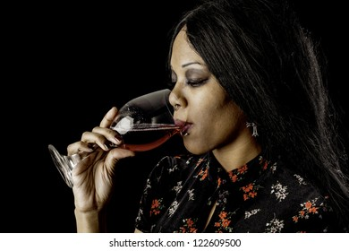 A sexy gothic african american drinking red wine from a glass against a dark background.