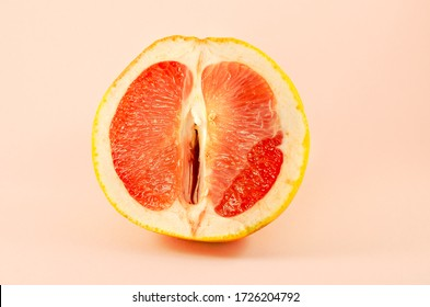 Sexy grapefruit, erotic concept. Sectional grapefruit is a symbol of the vagina and clitoris. Erotic half of grapefruit in a section. Half grapefruit a pastel background. Female vagina and clitoris.