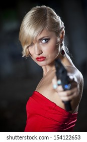 Sexy gun woman in retro look pointing gun