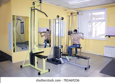 sexy guy with a naked torso. swings the back muscles and the press on the simulator. reflection in the mirror