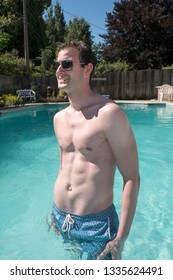 Sexy guy standing in an outdoor swimming pool waist deep in water. Fit model with defined abs in aviator sunglasses on a bright sunny day. Young white man in blue swimming suit.