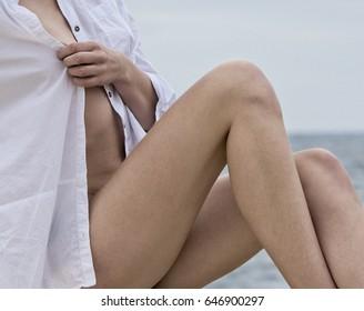 Sexy half naked woman. Naked sensual beautiful girl.Woman posing with the white linen shirt, summer.Fashionable caucasian white woman. Woman wearing light shirt. Fragment photo of half naked girl
