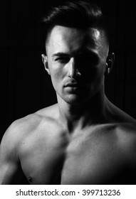 Sexy handsome charming serious powerful young guy brunet with fashion hairstyle looking straight posing with bare shoulders on dark background studio closeup black and white portrait