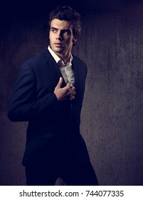 Sexy handsome male model posing in blue fashion suit and white style shirt on dark shadow background. Toned color portrait