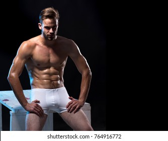 Sexy handsome male model in underwear. Handsome muscular man in white boxer shorts. Handsome naked muscular man in white underwear with beautiful sexy torso, which sits on white table in studio.