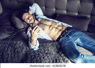 Sexy handsome man laying with open shirt on his bed with cell phone, looking at screen, typing or surfing the internet