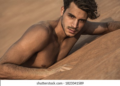 Sexy handsome topless male model lying on the desert sand. Beauty portrait.
