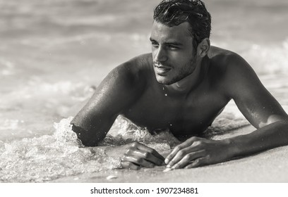 Sexy handsome topless male model relaxing happy in the ocean water on the beach. Black and White.