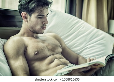 Sexy handsome young man laying shirtless on his bed next to window, reading a book