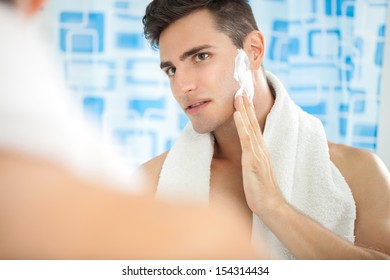 Sexy handsome young man putting on shaving cream on cheek