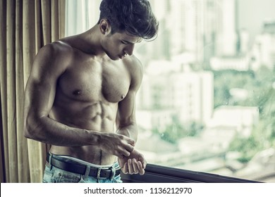 Sexy handsome young man standing shirtless in his bedroom next to window curtains, adjusting wrist watch