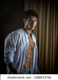 Sexy handsome young man standing and dressing, in his bedroom next to window curtains, looking at camera with shirt open on naked muscular torso