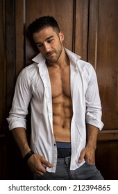 Sexy handsome young man standing in white open shirt with a smile in front of wood closet doors