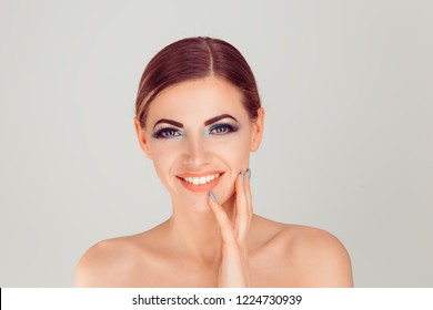 Sexy, happy and beautiful. Portrait of beautiful woman smiling hand touching face isolated on a light gray white background wall.