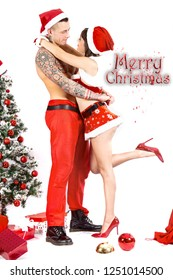 Sexy and happy couple embraced next to Christmas tree with gifts. She with sexy Christmas dress, high-heeled shoes, miniskirt, his bare chest with tattoos. With red writing Merry Christmas and sparks