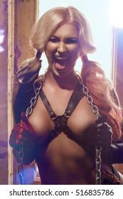 Sexy harlequin woman with batt on dark background