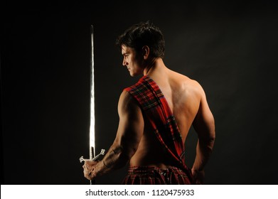 The sexy highlander flexes his muscles.