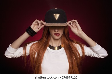 Sexy hip-hop woman in cap with long red hair. Fashion portrait of modern girl in cap