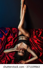 Sexy and hot brunette woman lying on red silk in seductive lace lingerie.
