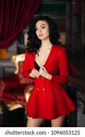Sexy and hot girl in red dress undresiing, holding clothe in hand, and touching hair. Woman with professional make up and volumed hairstyleseductive touching her chest. Library interior.