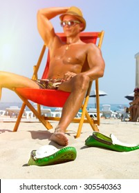Sexy hot muscular Man on beach looking to camera smiling ,wearing hipster hat, sunglasses,military printed trousers.Young male model enjoying beach with shoes off.Focus on shoes.