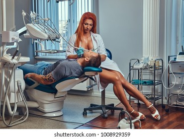 A Sexy hot redhead dentist woman, taking care of her patient.