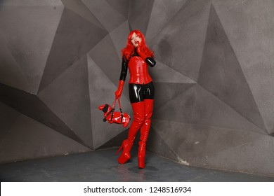 sexy kinky mistress woman posing in black latex rubber catsuit and red shiny corset with huge thigh high heels boots and with fashionable dog with gag bag