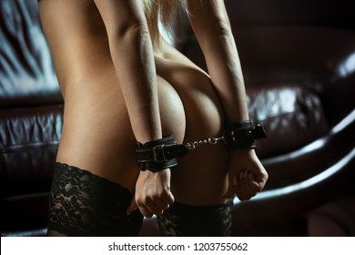 Sexy lady in bdsm outfit. Beauty woman with attractive body in lingerie. Female ass in underwear. Naked girl. Bound woman. Handcuffed hands