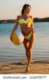 sexy lady with beach ball in yellow swimsuit at sunset