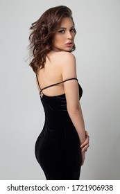 Sexy lady in black slim dress posing over grey background. Seductive brunette girl in sexy fashion clothes