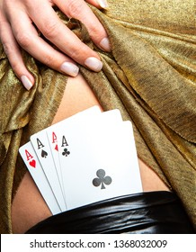 Sexy lady in golden color dress with poker cards combination over black stocking legs. Concept Nightlife.