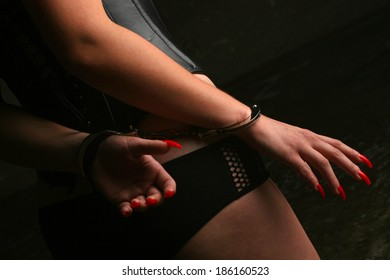 Sexy lady with handcuffs by the wall