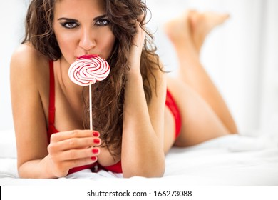 Sexy lady licking a lollipop while lying in bed